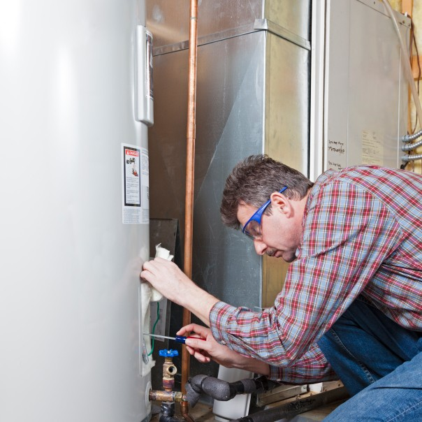 A plumber is performing maintenance on a residential water heater